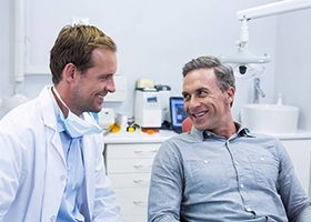 Smiling older man and woman talking to dental team member