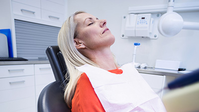 Woman in dental chair with eyes closed