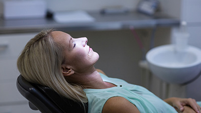 Relaxing woman in dental exam chair
