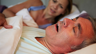 Frustrated woman in bed next to snoring man