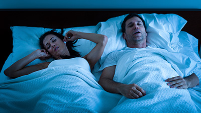 Woman plugging ears inbed next to snoring man