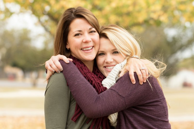 A mother and daughter hugging outside.