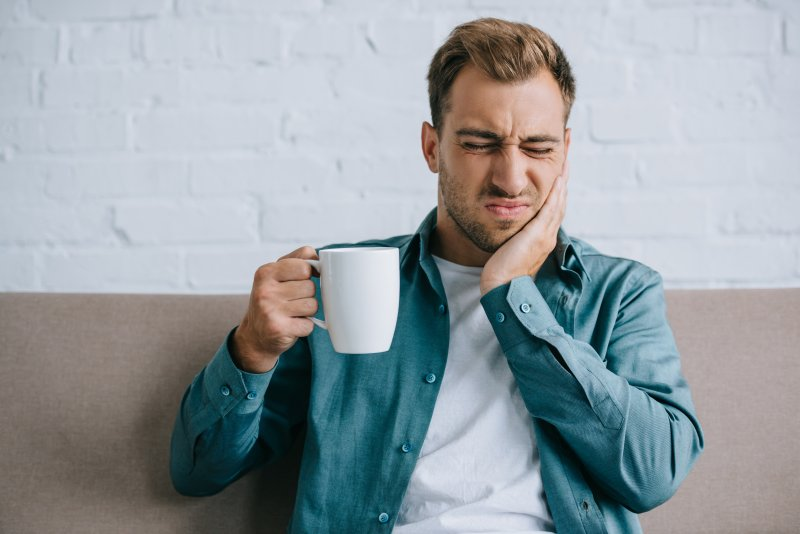 Man with coffee mug rubbing jaw due to pain