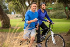 Man and woman without tooth pain smiling outside while working out