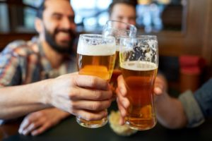Group of people clinking glasses of beer together