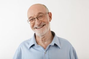 Older man with greying hair smiling with glasses
